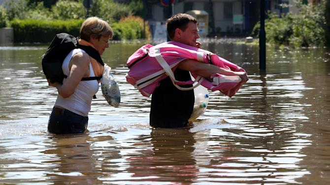 Inhabitants carry belongings through the floods of river Elbe in Magdeburg, eastern Germany, Saturday June 8, 2013. German news agency dpa said people in Magdeburg in Saxony-Anhalt were anxiously awaiting the crest of the Elbe river on Saturday, while residents further upstream were starting to clean up the debris that was left along the river. In Magdeburg, authorities evacuated a nursing home and turned off electricity in several parts of the city.  High water levels were also reported from Hungary, Slovakia and the Czech Republic, while thousands of people in Austria were busy shoveling away the mud left by the receding floodwaters of the Danube.   (AP Photo/dpa,Jens Buettner)