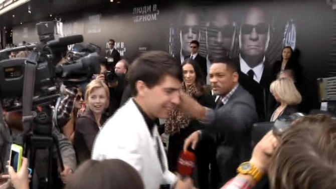 "In this video image taken from AP video U.S. actor Will Smith, center right, slaps reporter Vitalii Sediuk, white suit, from the Ukrainian television channel 1+1  on the red carpet before the premiere of ""Men in Black III"" Friday May 18, 2012 in Moscow. Hollywood star Will Smith has slapped a male television reporter who tried to kiss him before the Moscow premiere of ""Men in Black III."" Smith pushed him away and then slapped him lightly across the cheek with the back of his left hand.   (AP Photo via AP video)"