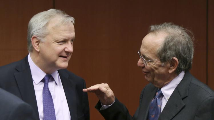 Rehn listens to Padoan during an eurozone finance ministers meeting in Brussels