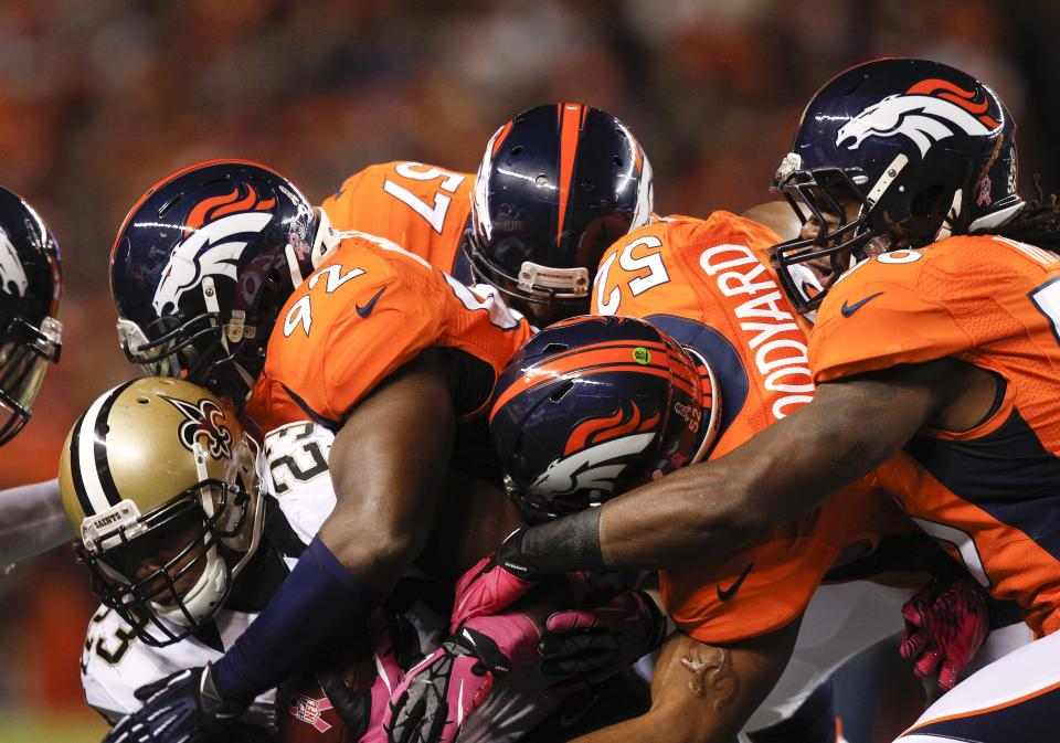 The Denver Broncos defense piles up on New Orleans Saints running back Pierre Thomas (23) in the first quarter of an NFL football game, Sunday, Oct. 28, 2012, in Denver. (AP Photo/David Zalubowski)