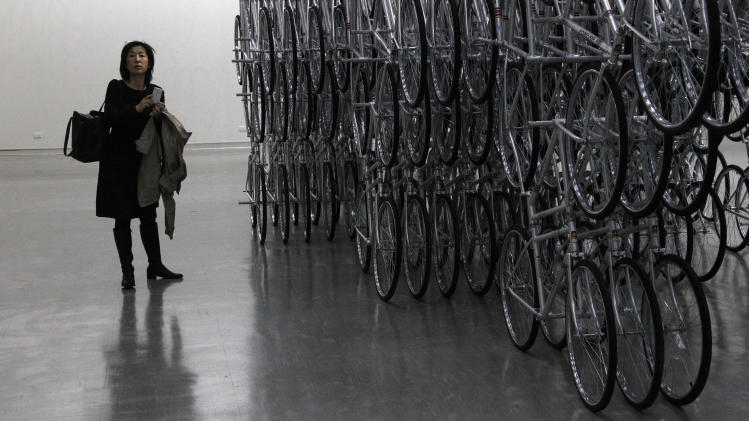 """A visitor stands at an instillation entitled """"Forever Bicycles"""" by the Chinese artist and activist Ai Weiwei at the """"Ai Weiwei is Absent"""" exhibition in the Taipei Fine Arts Museum in Taipei, Taiwan, Friday, Oct. 28, 2011. (AP Photo/Wally Santana)"""