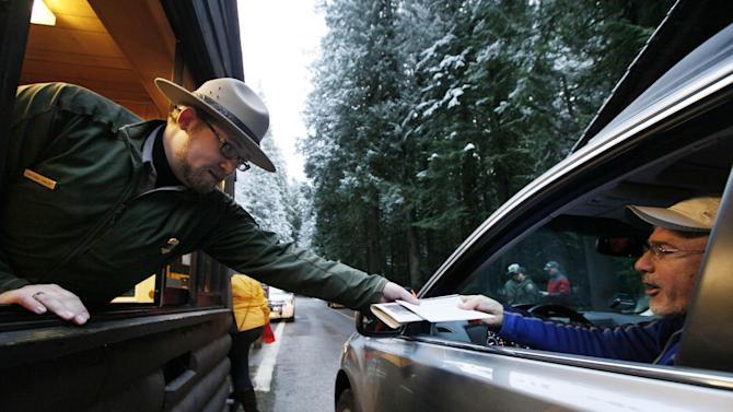 FILE - In this Jan. 7, 2012 file photo, Mount Rainier  National Park Ranger Matt Chalup, left, hands park information to one of the first visitors to the park at the Nisqually entrance near Ashford, Wash. The politics have been fierce and the fingerpointing incessant. Come March 1, the across-the-board federal spending cuts called sequestration go into effect, launching a new season of economic uncertainty for a nation still trying to shake off a recession. A look at the cuts, how much they amount to and who they will affect -- in question and answer form. (AP Photo/Elaine Thompson, File)