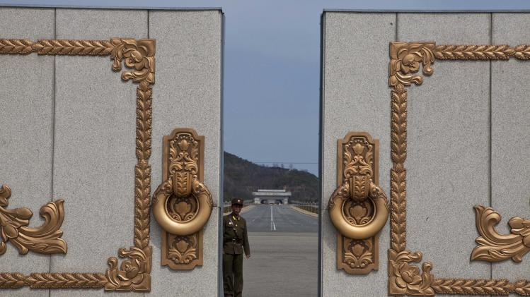 A North Korean soldier guarding the entrance to Pyongyang's Kumsusan mausoleum, where the bodies of the late leaders Kim Il Sung and Kim Jong Il lie embalmed, looks back through the doors of the main gate Monday, April 15, 2013. North Koreans turned out on Monday to mark the 101st birthday of Kim Il Sung. (AP Photo/David Guttenfelder)