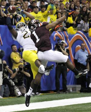 Michigan wide receiver Junior Hemingway (21) pulls in a touchdown reception as Virginia Tech safety Antone Exum (1) covers during the third quarter of the Sugar Bowl NCAA college football game in New Orleans, Tuesday, Jan. 3, 2012. (AP Photo/Bill Haber)
