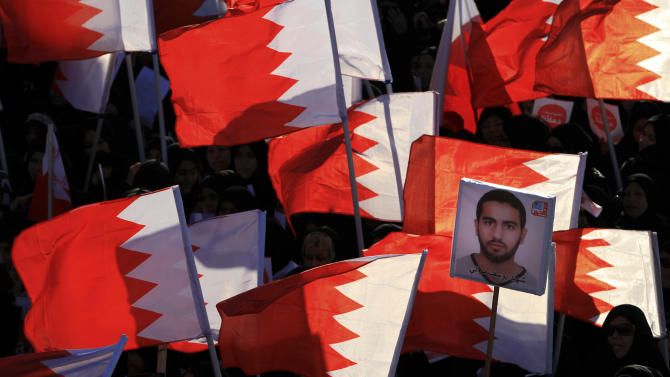 """Bahraini anti-government protesters wave national flags and carry signs during a march called by several opposition groups to demand freedom for political prisoners and democracy, in Muharraq, Bahrain, on Monday Feb. 4, 2013. Arabic on the image at right reads, """"Martyr Yousef Mowali."""" (AP Photo/Hasan Jamali)"""