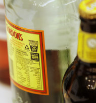 A small label with a health warning is displayed on an alcohol bottle in Sydney, Australia, Tuesday, July 12, 2011. Australia's liquor industry has launched a voluntary program on Tuesday to label its products with health warnings. (AP Photo/Rick Rycroft)