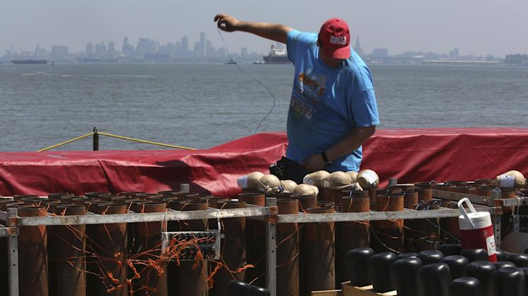 A Pyro Spectaculars by Souza worker loads shells into mortars on a barge docked in the Staten Island borough of New York, Saturday, June 29, 2013. Forty thousand shells are being loaded onto four barges in preparation for the Macy's Fourth of July fireworks display. (AP Photo/Mary Altaffer)