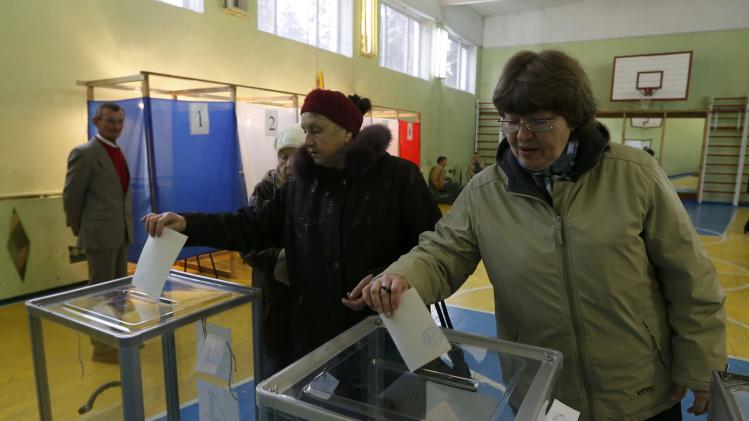 Women cast their ballots during voting in a referendum at a polling station in Simferopol