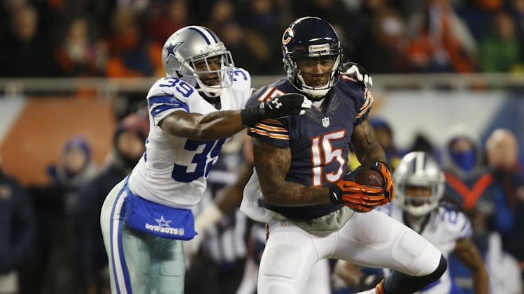 Chicago Bears wide receiver Brandon Marshall (15) makes a catch under pressure from Dallas Cowboys cornerback Brandon Carr (39) during the first half of an NFL football game, Monday, Dec. 9, 2013, in Chicago