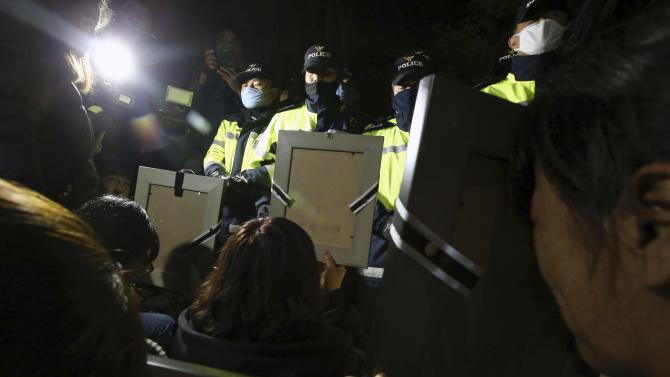 Policemen stop parents holding portraits of their children who were died on sunken passenger ship Sewol, from marching towards Presidential Blue House in Seoul