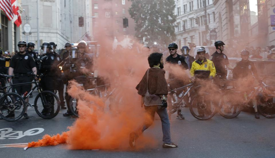 A protester walks away after placing a smoke device on the ground in front of police officers during a May Day march that began as an anti-capitalism protest and turned into demonstrators clashing with police lies on the ground next to police batons, Wednesday, May 1, 2013, in downtown Seattle. (AP Photo/Ted S. Warren)