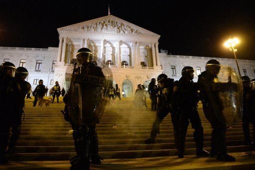 <p>Police officers stand guard outside the Portuguese Parliament in Lisbon as demonstrators protest against the Portuguese government's 2013 austerity budget. The Portuguese parliament adopted on Wednesday a 2013 austerity budget that includes draconian tax increases required by international creditors.</p>