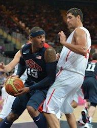 US forward Carmelo Anthony (L) vies with Tunisian forward Mohamed Hadidane during the Men&#39;s preliminary round group A basketball match of the London 2012 Olympic Games Tunisia vs USA at the basketball arena in London. USA won 110 to 63