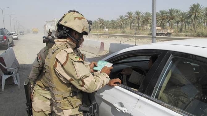 A member of the Iraqi security force checks identification papers at a checkpoint in Latifiya