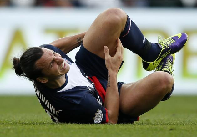 Paris St Germain's Ibrahimovic holds his leg after a collision with Bastia's Palmieri during their French Ligue 1 soccer match in Paris