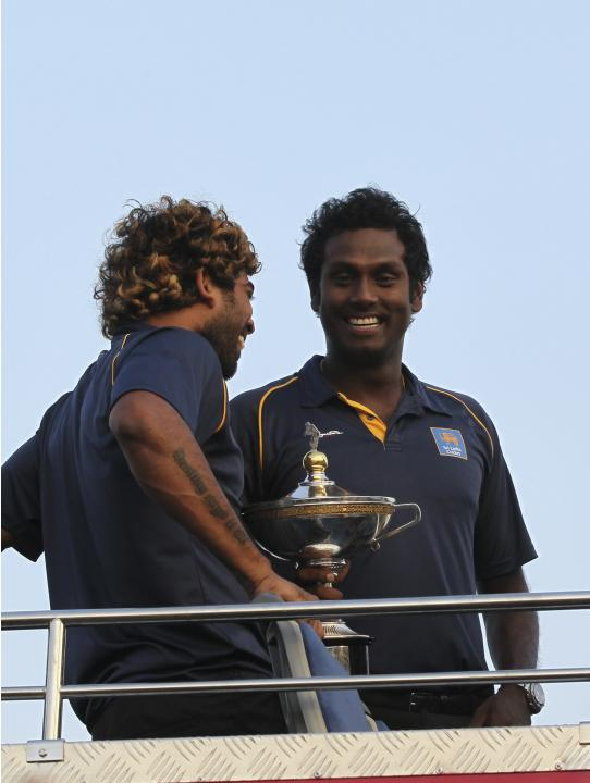Sri Lankan cricket captain Angelo Mathews, right, shares a light moment with bowler Lasith Malinga standing in an open bus, as they return from Bangladesh after winning the Asia Cup in Colombo, Sri La