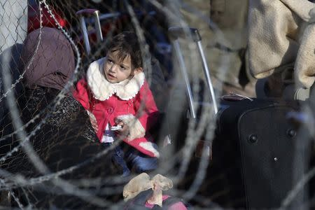 Palestinian girl, hoping to cross into Egypt with her mother, is pictured through a fence as she waits at the Rafah crossing between Egypt and the southern Gaza Strip