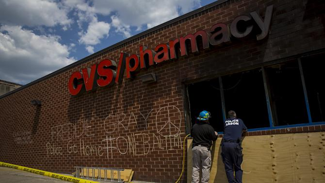 Investigators are seen at a pharmacy that burned at Pennsylvania Ave and North Ave in Baltimore, Maryland