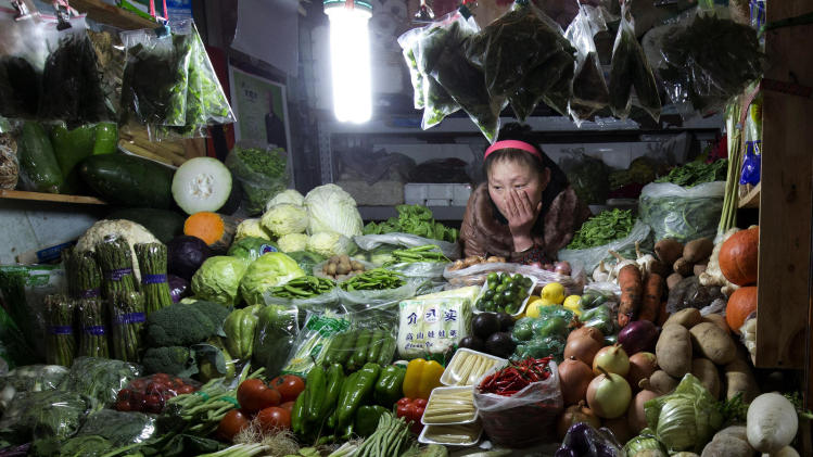 A vegetable vendor waits for customers at a market in Beijing Friday, Jan. 11, 2013. China's inflation spiked to a six-month high in December after a freezing winter pushed up vegetable prices, possibly complicating efforts to sustain a shaky economic recovery, the National Bureau of Statistics reported Friday. (AP Photo/Ng Han Guan)