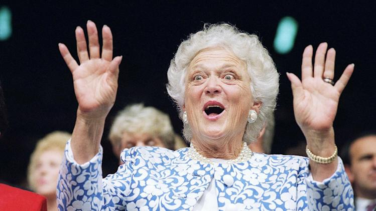 FILE - In this Aug. 18, 1992, file photo, first lady Barbara Bush reacts to Sen. Phil Gramm, who delivered the keynote address to the Republican National Convention at the Houston Astrodome. Expecting Ann Romney and Michelle Obama to take the stage to assure Americans that their men are swell husbands and fathers may sound like a holdover from the 1950s, but it's a relatively recent political convention tradition. It wasn't until 1992 that Bush pioneered the wifely testimonial. She was assigned a prime Republican convention slot in hopes that her matronly charm would steady her husband's wobbly re-election bid. (AP Photo/Marcy Nighswander, File)