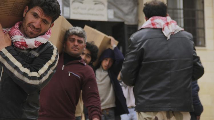 Men carry boxes of aid to be distributed to residents during the launching of a humanitarian campaign called 'In Green' in Kafranbel, Idlib countryside