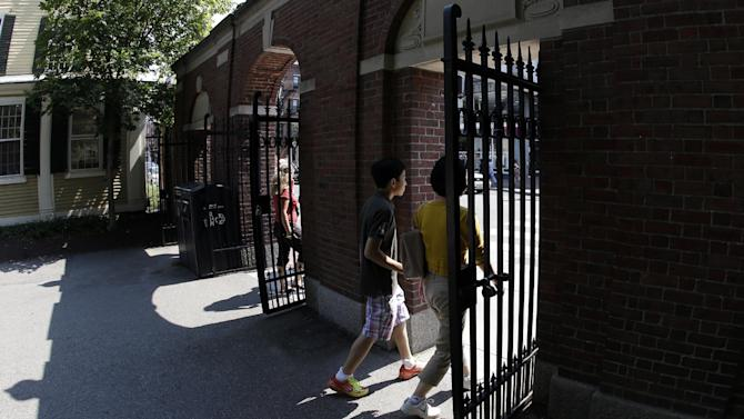 Pedestrians walk through a gate on the campus of Harvard University in Cambridge, Mass. Thursday, Aug. 30, 2012. Dozens of Harvard University students are being investigated for cheating after school officials discovered evidence they may have wrongly shared answers or plagiarized on a final exam. Harvard officials on Thursday didn't release the class subject, the students' names, or specifically how many are being investigated. (AP Photo/Elise Amendola)