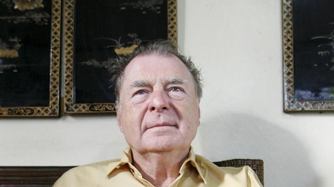 File photo of U.S. scientist Richard Heck of the University of Delaware holding his book during a Reuters interview at his home in Quezon City
