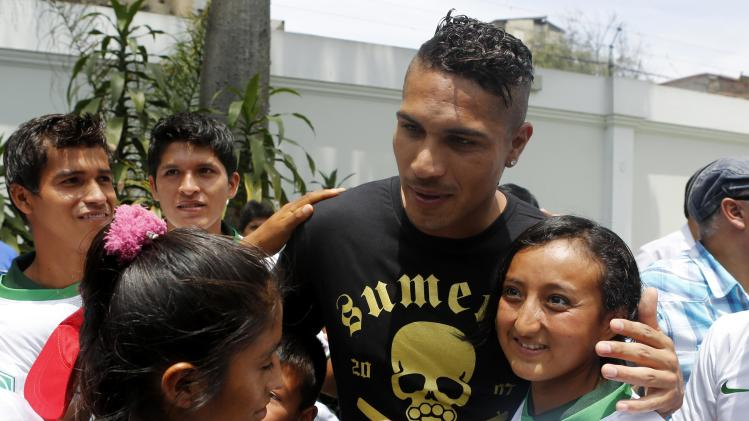 Peruvian soccer player Paolo Guerrero poses with children from soccer schools during a Christmas event in Lima