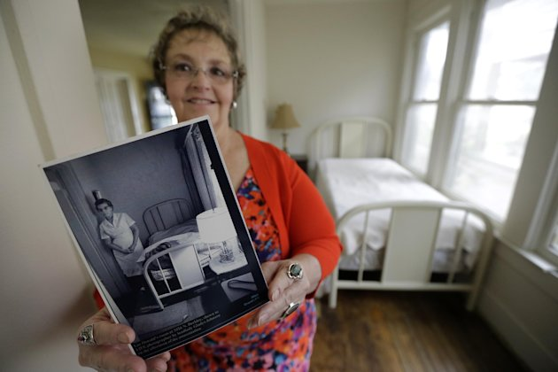 In this May 15, 2013 photo, Patricia Hall holds a photograph of her grandmother, Gladys Johnson, while standing in the 5-by-14 room that Lee Harvey Oswald rented in 1963 at her family's boarding house in Dallas. Oswald stayed at the red brick house with white trim during the week while working his new job at the Texas School Book Depository, and on the weekends he returned to the suburb of Irving where his wife lived. Hall said she's been considering selling the house for years, but decided the time was right as this year marks the 50th anniversary of Kennedy's assassination in downtown Dallas. (AP Photo/Tony Gutierrez)