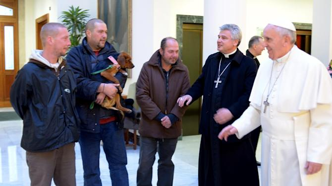 """In this picture provided by the Vatican newspaper L'Osservatore Romano, Pope Francis, right, is flanked by Vatican Almoner Archbishop Konrad Krajewski as he welcomes four men at the Vatican, Tuesday, Dec. 17, 2013. Four homeless people, one of them bringing his dog, helped Pope Francis celebrate his 77th birthday at the Vatican Tuesday. They live on the street in the Rome neighborhood just outside the Holy See's walls and were invited by the Vatican official in charge of alms-giving to attend the morning Mass which Francis celebrates daily at the hotel where he lives on Vatican City grounds, the Vatican said. One of the men held his dog as he was presented to Francis after the guests chatted following Mass. The Vatican also said Francis invited his household help to join him in a """"family-like"""" atmosphere, and he spoke of them one by one during his homily. (AP Photo/L'Osservatore Romano)"""