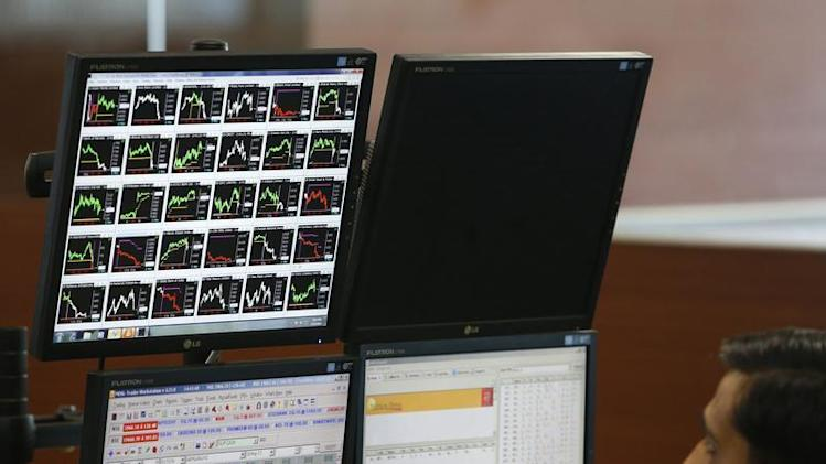 A broker monitors a screen displaying live stock quotes on the floor of a trading firm in Mumbai