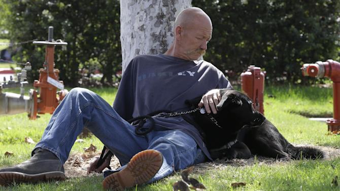 In this photo taken Oct. 6, 2012, Don Matyja, a homeless Army veteran poses for a picture with his dog Tyson at Lions park in Costa Mesa, Calif. The posh California coastal town recently passed a law banning patrons from lounging on furniture in its public libraries, having poor personal hygiene or emitting an odor bothers others. The ordinances are the latest in a rash of law-making in Orange County cities that some see as thinly veiled attacks on the homeless. But lawmakers defend the policies as necessary to ensure safety, protect public property and guarantee access to communal spaces. (AP Photo/Chris Carlson)