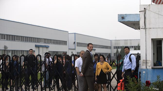 U.S. Embassy employees stand outside the closed gate at Specialty Medical Supplies plant where American Chip Starnes, co-owner of the plant, not in picture, is being held hostage at the Jinyurui Science and Technology Park in Qiao Zi township of Huairou District, on the outskirts of Beijing, China Monday, June 24, 2013. An American executive said Monday Starnes has been held hostage for four days at his medical supply plant in Beijing by dozens of workers demanding severance packages like those given to co-workers in a phased-out department. (AP Photo/Andy Wong)