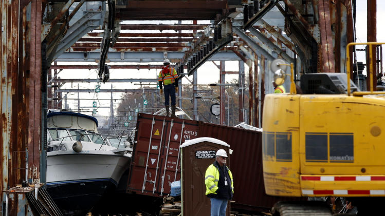 Workers try to clear boats and debris from the New Jersey Transit Morgan draw bridge Wednesday, Oct. 31, 2012, in South Amboy, N.J., after Monday's storm surge from Sandy pushed boats and cargo containers onto the train tracks. Travel in the Northeast creaked back into motion on Wednesday, a grinding, patchy recovery that made it clear that stranded travelers will struggle to get around for days to come. (AP Photo/Mel Evans)(AP Photo/Mel Evans)