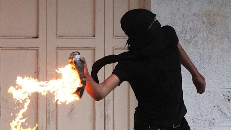 A Palestinian demonstrator throws a petrol bomb towards Israeli border guards in the West Bank city of Hebron during a demonstration on November 27, 2013