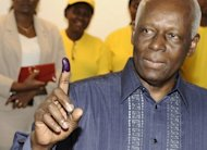 Angolan President Jose Eduardo Dos Santos shows his ink-marked finger as proof of his ballot cast at a polling station in Luanda on August 31. Dos Santos took a large lead in the first returns from this week's parliamentary vote