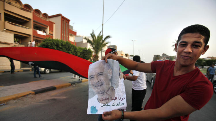 "A Libyan holds a poster of Moammar Gadhafi reading ""We did you a favour, we gave you a hair cut for Free"" in a street of Jamal Goubtan district inTripoli, Libya, Thursday, Sept. 1, 2011. A TV station is quoting Moammar Gadhafi as warning that tribes loyal to him in key strongholds are armed and won't surrender to Libyan rebels. Thursday's report on Syrian-based Al-Rai TV comes as the rebels who have seized control of most of the country extended by a week a deadline for the surrender of Gadhafi's hometown of Sirte - originally set for Saturday.(AP Photo/Abdel Magid Al Fergany)"