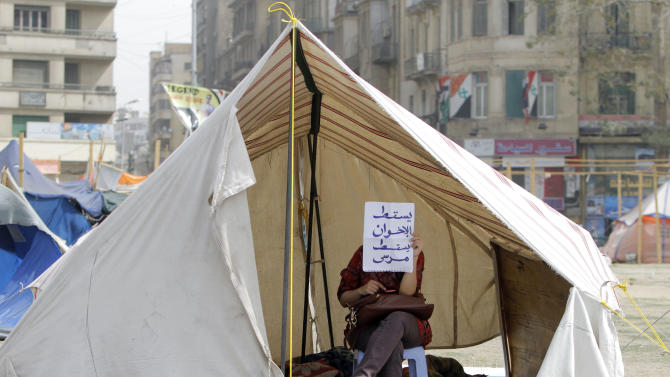 """An Egyptian activist holds a piece of paper with Arabic that reads, """"down with the Muslim Brotherhood, down with Morsi,"""" in a tent in Tahrir Square, the focal point of the Egyptian revolution, in Cairo, Egypt, Sunday, March 3, 2013. Security forces re-opened Tahrir Square removing barbed wire across the entrances to allow traffic to flow normally for the first time in months. Protesters have held a sit-in in the square since Nov. 22, 2013 after President Morsi issued a controversial constitutional declaration that rendered his decisions above judicial supervision. (AP Photo/Amr Nabil)"""
