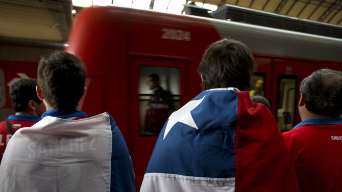 Chile soccer fans, some wearing a representation of their country's national flag, wait on a subway platform for a passenger car, on their way to Itaquerao Stadium, to see the World Cup group B match against the Netherlands in Sao Paulo, Brazil, Monday, June 23, 2014. Both teams having already qualified for the round of 16, Monday's match will decide which of them wins Group B. (AP Photo/Dario Lopez-Mills)