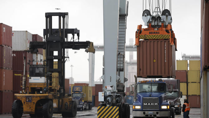 FILE - In this Dec. 18, 2012 file photo, a truck driver watches as a freight container, right, is lowered onto a tractor trailer by a container crane at the Port of Boston in Boston. The crane and a reach stacker, left, are operated by longshoremen at the port. The longshoremen's union may strike if they are unable to reach an agreement on their contract, which expires Dec. 29, 2012. A walkout by dock workers represented by the International Longshoremen's Association would bring commerce to a near halt at ports from Boston to Houston. (AP Photo/Steven Senne, File)