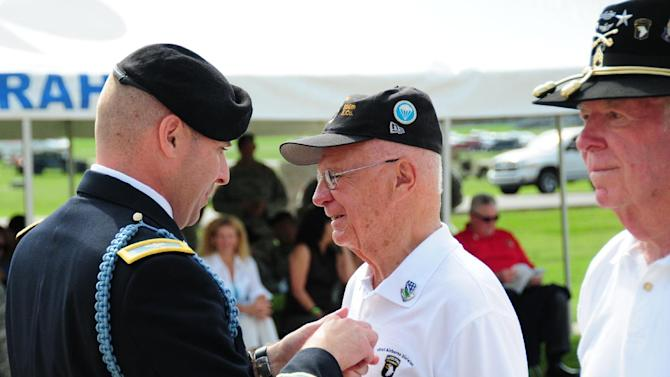 In this July 20, 2012 photo provided by the U.S. Army, Col. Val Keaveny Jr., left, commander of the 4th Brigade Combat Team, 101st Airborne Division, pins Herbert Suerth Jr., a World War II veteran of Easy Company, 506th Parachute Infantry Regiment, as a Distinguished Member of the Regiment during a ceremony at Fort Campbell, Ky. This week, thousands of active-duty soldiers and veterans are gathering at Fort Campbell, Ky., to honor the division that was created 70 years ago, even as its current soldiers prepare to leave for Afghanistan. (AP Photo/U.S. Army)