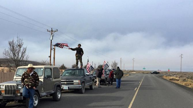 People wave American flags near the Malheur National Wildlife Refuge, Thursday, Feb. 11, 2016, near Burns, Ore. The last four armed occupiers of the national wildlife refuge in eastern Oregon said they would turn themselves in Thursday morning, after law officers surrounded them in a tense standoff.  (AP Photo/Rebecca Boone)