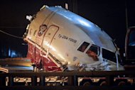 <p>A truck removes the cabin of the Tu-204 jet from its crash site near the Vnukovo airport outside Moscow on December 29, 2012. Russian medics began Sunday identifying the bodies of four crew killed when the passenger jet careened off the runway of a Moscow international airport and smashed into a highway.</p>