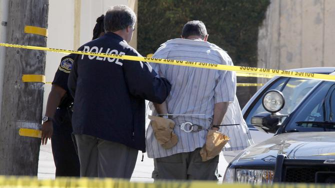 Police officers lead Scott Evans Dekraai to a patrol car after arresting him following a shooting at the nearby Salon Meritage that left eight people dead and one critically injured in Seal Beach, Calif., Wednesday, Oct. 12, 2011. Friends of the salon owner and other employees said Dekraai, 42, was the ex-husband of a stylist who worked there. (AP Photo/Reed Saxon)