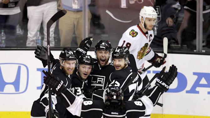Los Angeles Kings' Jeff Carter (77), Tyler Toffoli (73), Jake Muzzin (6), Dustin Brown (23) and Drew Doughty (8) celebrate a goal by Muzzin as Chicago Blackhawks' Jonathan Toews (19) skates behind them during the first period of Game 4 of the Western Conference finals of the NHL hockey Stanley Cup playoffs on Monday, May 26, 2014, in Los Angeles