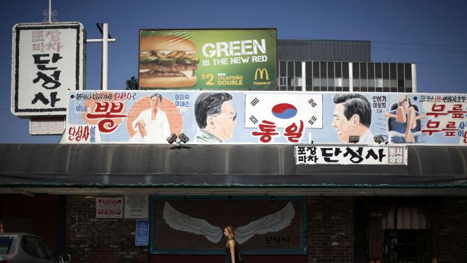 Woman walks past a mural of a pair of wings, under another mural depicting former North Korean leader Kim Jong Il and former South Korean president Kim Dae-jung, hanging above Dan Sung Sa restaurant and bar in Koreatown area of Los Angeles