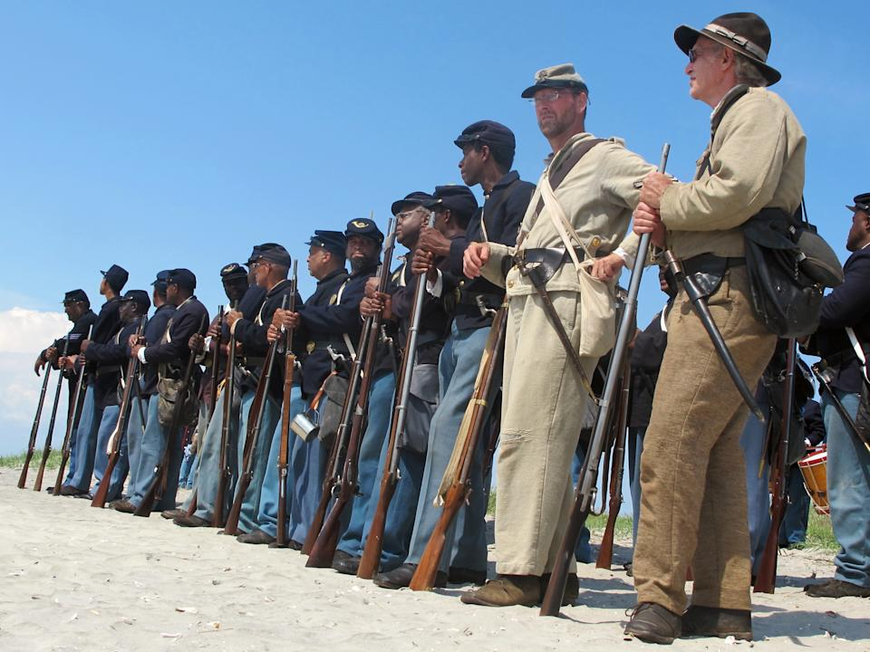"Re-enactors representing both North and South stand on Morris Island near Charleston, S.C., on Thursday, July 18, 2013 during a observance of the 150th anniversary of the charge of the black 54th Massachusetts Volunteer Infantry in a fight commemorated in the film ""Glory."" (AP Photo/Bruce Smith)"
