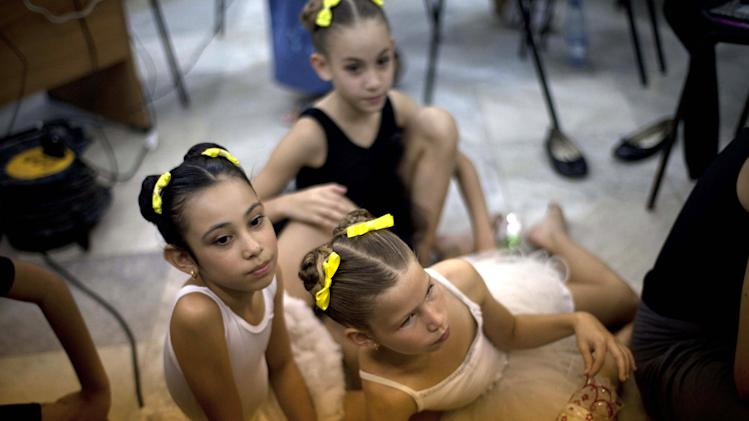 In this April 3, 2013 photo, three young ballet students watch a ballet class at the National School of Ballet in Havana, Cuba.  The school, housed in a graceful building that occupies a full half-block in colonial Old Havana, not only teaches dance, but subjects like language, math and history. (AP Photo/Ramon Espinosa)