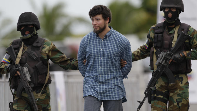 Dominican-American Eduardo Acosta Mejia is escorted in handcuffs by National Guard officers during his deportation to Colombia at the Simon Bolivar airport in Maiquetia, near Caracas, Venezuela, Wednesday, Nov. 14, 2012. Acosta is a naturalized U.S. citizen who was born in the Dominican Republic, and is wanted by Colombian authorities on drug trafficking charges. (AP Photo/Ariana Cubillos)