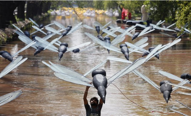 A man adjusts a model of dragonfly installation over a canal in Lahore